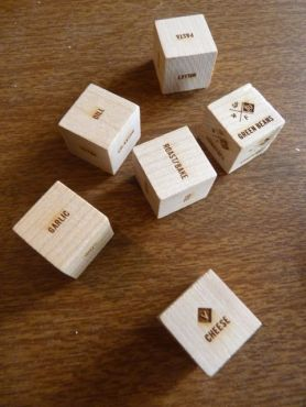 Six wooden dice with names of ingredients stamped on the faces.